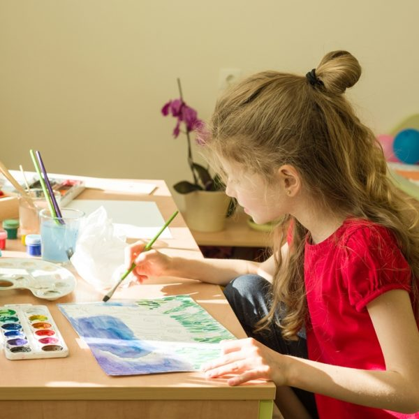 The child is 7 years old, draws watercolor at the table at home. Child creativity, recreation, development